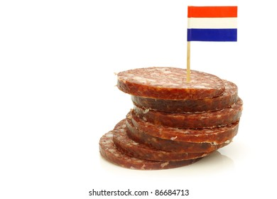 """pieces of traditional dutch sausage called """"boerenmetworst"""" with a dutch flag toothpick on a white background"""