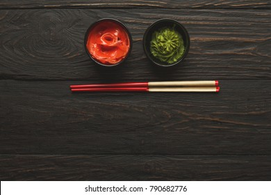 Pieces of traditional japanese tablewear. Red chopsticks with hierogliphs, small black bowls with ginger and wasabi on dark wooden table. Top view, flat lay, copy space, background