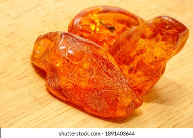 Pieces of transparent amber with inclusions on a yellow background. A semi-precious stone made from petrified resin. Material for jewelry and ornaments. Copal. Sun stone. Fossil resin.  Insects