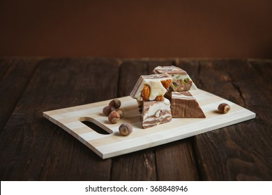 Pieces of Turkish halva with nuts on brown background