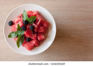 Pieces of watermelon, blackberries and mint leaves on a white plate