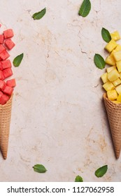 Pieces of watermelon and pineapple in a waffle cone on a marble background. Top view