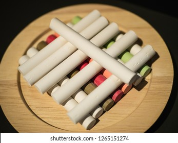 Pieces of white and colorful chalk on a plate, rowed up