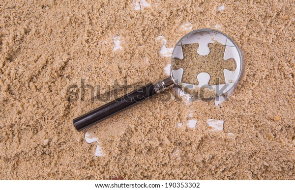 Pieces of white jigsaw puzzle buried in sand with magnifying glass