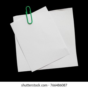Pieces of white note paper with paperclip on a black background. copy space