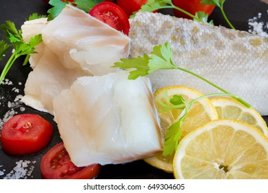 Pieces of white raw salted  codfish with tomatoes and parsley on slate plate