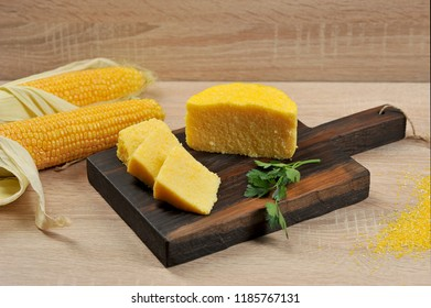 Pieces of yellow hominy on a wooden board. In the background are two cobs of corn. Close-up. Light background.