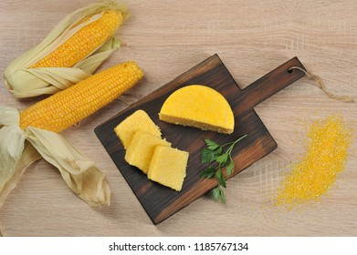 Pieces of yellow hominy on a wooden board. In the background are two cobs of corn. Close-up. View from above. Light background.