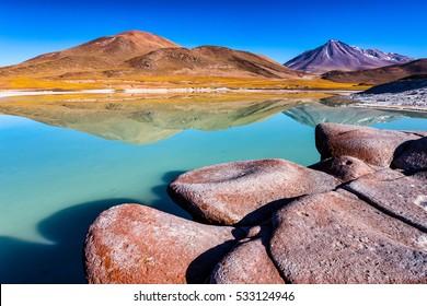 Piedras Rojas, Cerro Caichinque mirrored in the lake and Vulcano Miniques in background. Atacama, Chile.