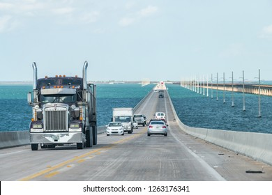 Piegon Key, USA - May 1, 2018: Point of view driving, moving in car on seven mile bridge landscape of Florida Keys water, atlantic ocean, many cars, trucks on Overseas Highway US1 road, route