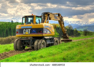 PIENINY MOUNTAINS, POLAND - MAY 11, 2016: Caterpillar excavator in the area with mountain landscape in background.