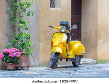Pienza, Italy; 8th May 2018; Bright Yellow Vespa Scooter Parked on the Street
