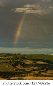 Pienza, Italy - July 7 2017: The rainbow over a farmland in Tuscany hills