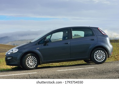 Pienza, Italy - October 13, 2012: Fiat Punto Evo car parked in front of wonderful landscape with hills with autumns grain fields and old castle seen through windows of car. World famous Vall d'Orcia