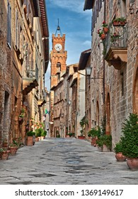 Pienza, Siena, Tuscany, Italy: the picturesque main street of the city with the ancient buildings and the clock tower on background
