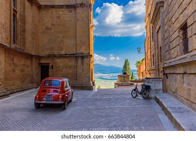 PIENZA, TUSCANY - JUNE 02, 2017 -   Red fiat 500 car parked in the alley of the city in tuscany