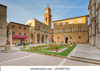 Pienza, Tuscany/Italy - May 10 2016: Idyllic square with fountain, town hall and the Duomo Santa Maria Assunta in Pienza.Tourists and local people on the Piazza in the old town of Pienza