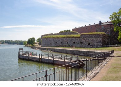 Pier and ancient fortifications in the historic fortress island Suomenlinna, Sveaborg in the Gulf of Finland in Finland on a summer day.