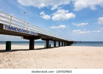 "Pier at the Baltic Sea coast with the town's name ""Timmendorfer Strand""on a placard"
