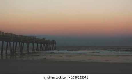 Pier at beach with colorful sunset with waves