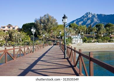 Pier, beach and sea in resort city of Marbella in Spain, Costa del Sol, Malaga province.