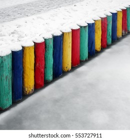 A pier of a boat station on a pond in a park. It made of wooden logs painted in saturated colors. They clearly stand out from the gray pre-winter scenery. Russia, Moscow, November 2016.