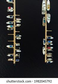 Eine Anlegestelle mit Booten auf dem Wasser. Von oben anzeigen. Shooting aus einer Drohne.