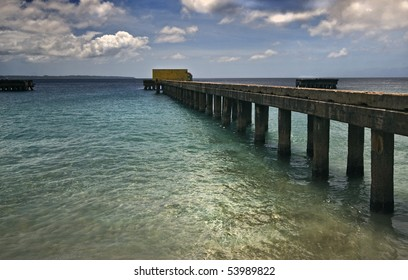 Pier at Crashboat Beach in Puerto Rico.  Dynamic clouds and vanishing point perspective create interest in the shot.  Great tropical image!