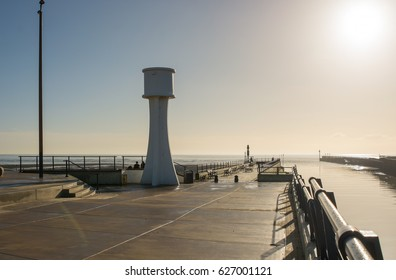 The pier at the entrance to Littlehampton harbour in West Sussex, England. Photographed into sun with high key lighting and silhoettes