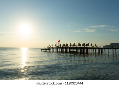 Pier with flag at sunrise in Kemer, Turkey