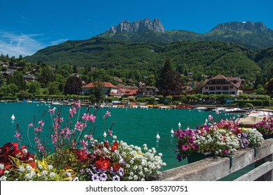 Pier with flowers and houses in the shore of the Annecy Lake with blue sky mountains landscape. Near the lovely village of Talloires. Department of Haute-Savoie, south-eastern France.