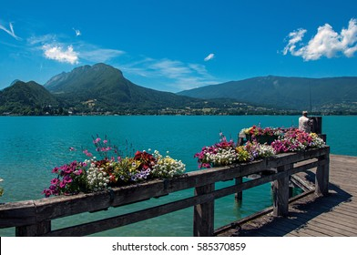 Pier with flowers on the Annecy Lake with blue sky mountains landscape. Near the lovely village of Talloires. Department of Haute-Savoie, south-eastern France.
