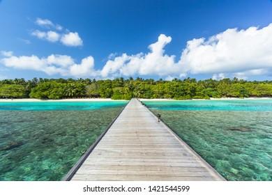 Pier following to a tropical Maldives island