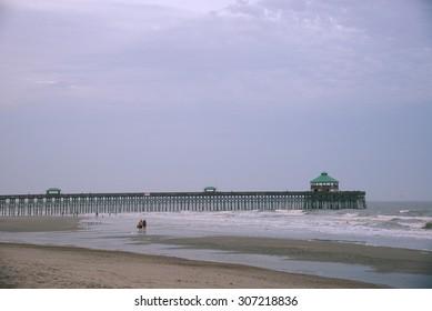 a pier at Folly beach in a cloudy evening