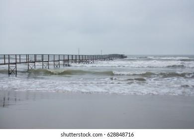 Pier and gloomy wavy sea