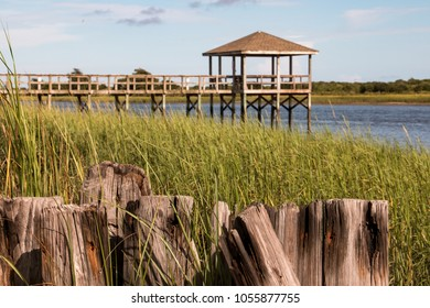 Pier with hut ocean isle north carolina nc with wooden planks and marsh in foreground