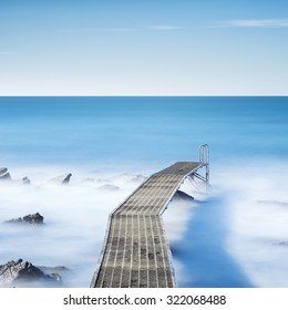 Pier or jetty and rocks on a blue ocean in the morning. Long Exposure