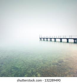 Pier or jetty silhouette in a foggy lake. Garda lake, Italy, Europe