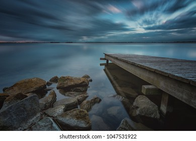 Pier or jetty, sunset blue panoramic landscape. rocks in the water. Long exposure
