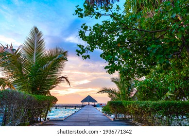 pier leading to the island at sunrise in the Maldives, the concept of luxury travel