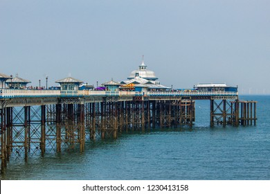 The pier in Llandudno Bay in Wales.  People along the pier having fun on the carousel and enjoying a weekend together. At 2,295 feet, the pier is the longest in Wales and the fifth longest in England.