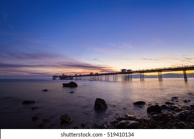The pier at Llandudno in North Wales, seen from the beach at sunrise with rocks near the shore in the foreground.