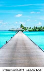 Pier at Maldives. Blue water, boats. Summer holidays photo.