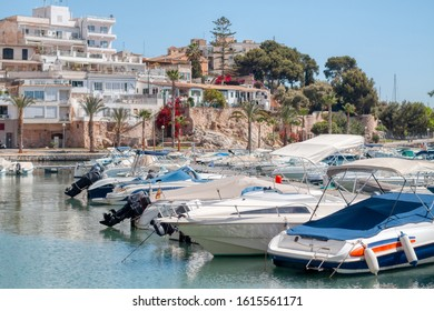 Pier with moored boats in port. High class lifestyle. Luxury summer vacation. Balearic islands, Majorca. Maritime walking. Yachting sport. Marina with anchored sailboats. Houses on background.