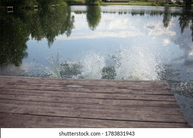 Pier near the lake. Splashing water near the platform. Wooden pier for diving into the water.