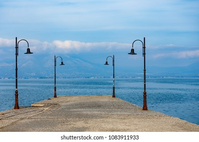 Pier near the sea with lamps framing the scene against a cloudy sky in Greece