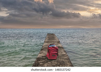 Pier in the ocean with dark clouds and a red backpack
