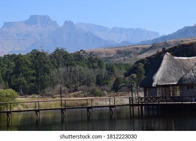pier on dam water with mountainous background blue skies green trees