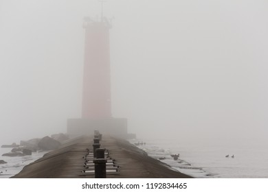 A pier on Lake Michigan with a lighthouse obscured by thick fog.  Sheboygan, Wisconsin, USA.