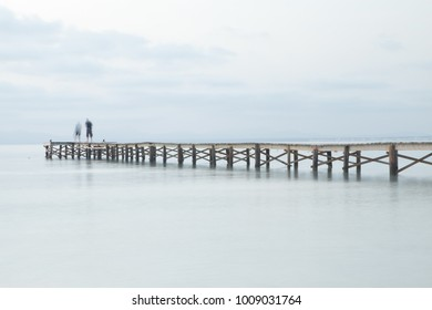 Pier on majorca with calm water and 2 persons, Spain